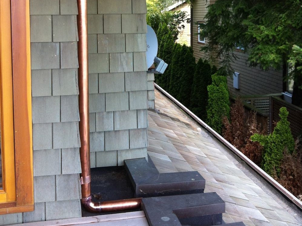 Hidden Gutter Repair | West Vancouver Home: copper downpipes used throughout to drain water from the upper eavestroughs.